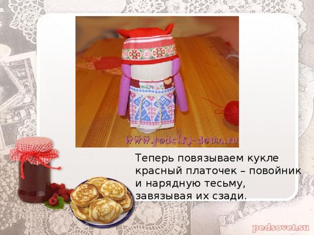 Теперь повязываем кукле красный платочек – повойник и нарядную тесьму, завязывая их сзади.