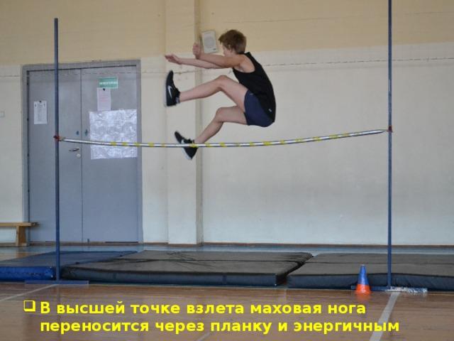 В высшей точке взлета маховая нога переносится через планку и энергичным движением опускается вниз-назад.