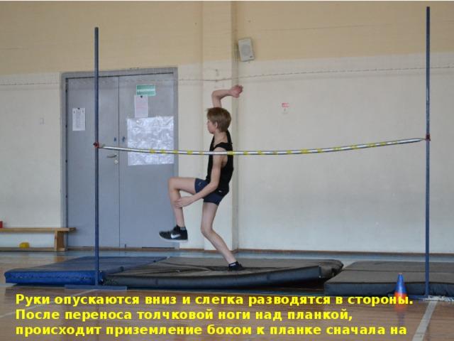 Руки опускаются вниз и слегка разводятся в стороны. После переноса толчковой ноги над планкой, происходит приземление боком к планке сначала на маховую, а затем на толчковую ногу.