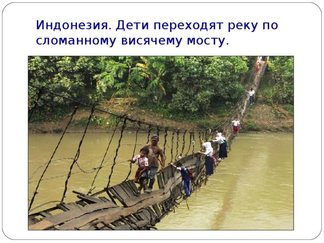 Индонезия. Дети переходят реку по сломанному висячему мосту.