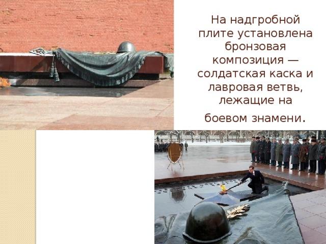 На надгробной плите установлена бронзовая композиция—солдатская каскаи лавровая ветвь, лежащие на боевом знамени .